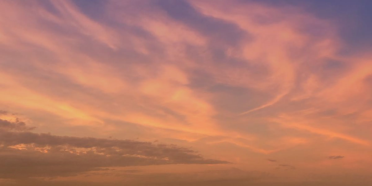 A photo of the evening sky with pink and purple clouds on the summer soltice