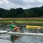 Two learn to row scullers on the water in their shells.